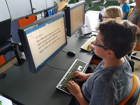 Mehrere Kinder sitzen am PC und lernen das Tastschreiben.