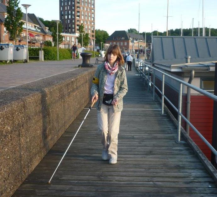 Eine junge Frau mit Langstock läuft über eine Brücke