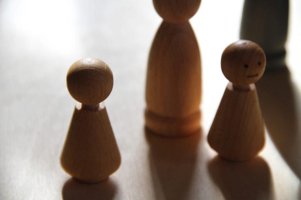 Unterschiedlich große Holzfiguren in Form von Menschen auf einem Brett