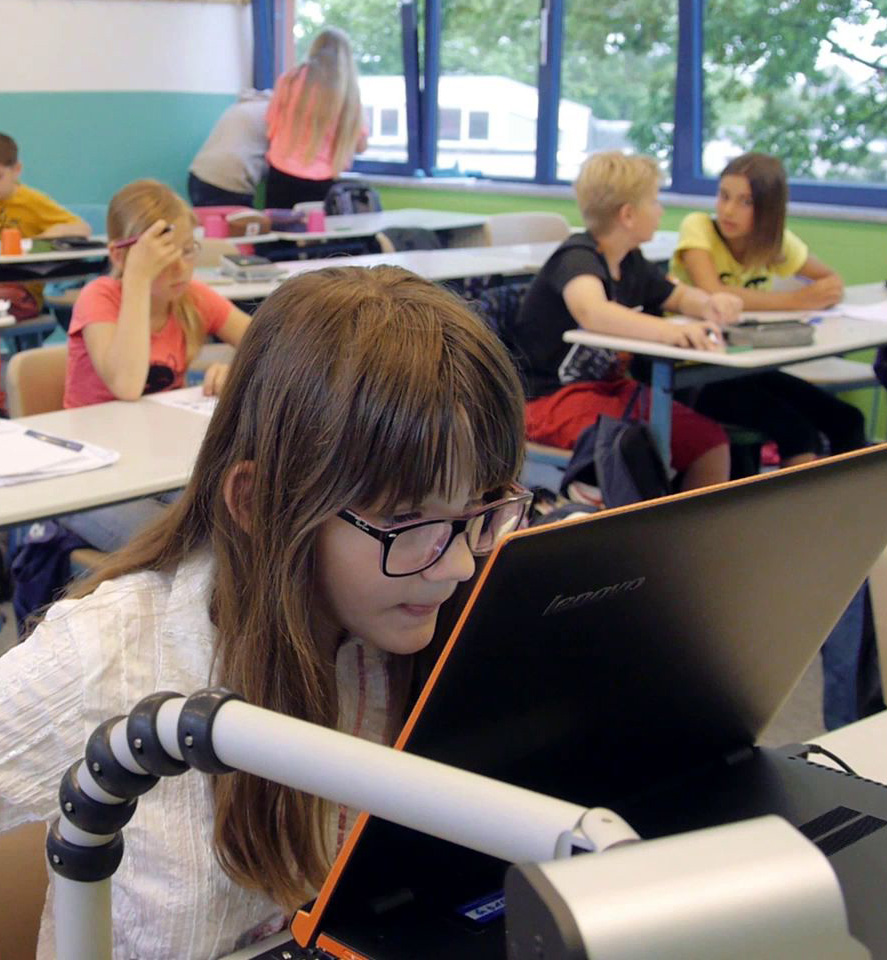 Eine Schülerin sitzt im Klassenraum vor ihrem Laptop und ihrer Tafelbildkamera.