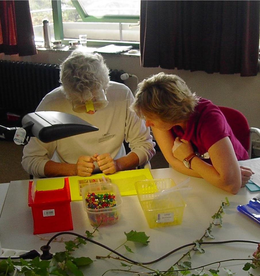 Zwei Seminarteilnehmerinnen basteln unter einer Simulationsbrille