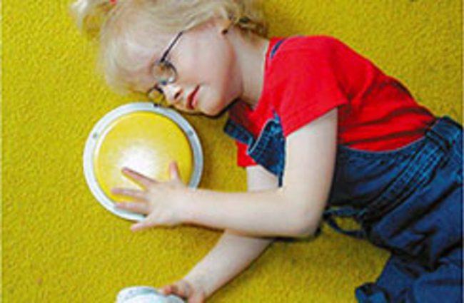 Ein Kind liegt auf einem Teppich und drückt mit der linken Hand auf einen großen Taster, während es in der linken Hand einen Talker hält