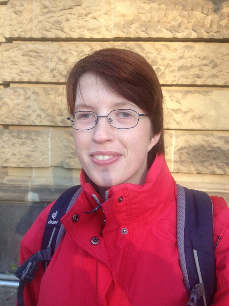 Porträt von einer Schülerin mit roter jacke und Rucksack auf dem Rücken.