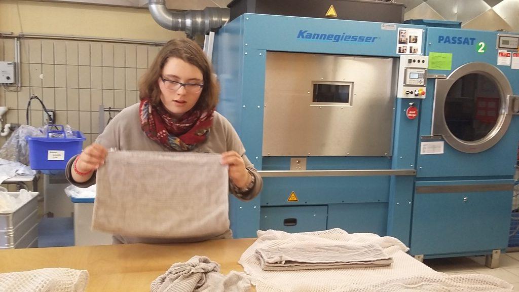 junge Frau vor einem Trockner, die Handtücher faltet