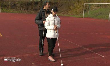 Klicksonartrainer Juan Ruiz mit einer Schülerin auf einem roten Sportplatz