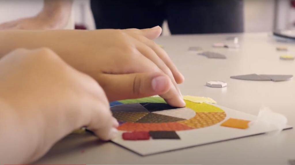 Zwei Hände berühren einen Kreis mit unterschiedlich beschaffenen und farbigen Flächen