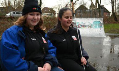 Elaine und Julina sitzen auf einer Bank. Julina hält ihren Langstock in der Hand. Bildtext: Hoffen auf viele Anregungen: Elaine Niedermirtl (l.) und Julina Seekopp vom Itzehoer Jugendparlament machen sich für die Attraktivierung der Skater-Anlage stark.